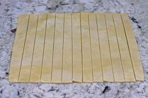 cortar masa de conos de hojaldre con merengue en tiras